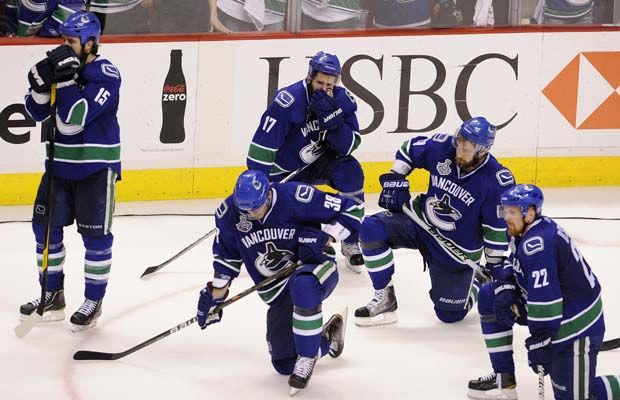 Vancouver Canucks players look on dejectedly as the Boston Bruins emerge victorious in the 2011 Stanley Cup Finals.